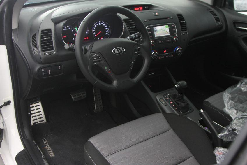 صورة المقصورة الأمامية لسيارة كيا سيراتو كوبيه بيضاء جديدة